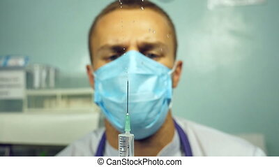 Portrait of young male caucasian doctor pouring a liquid from a syringe, taking off his protective mask and thinking. Medical worker preparing syringe for injection. Slow motion Close up