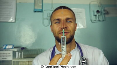 Portrait of young male caucasian doctor pouring a liquid from a syringe and smiling. Medical worker preparing syringe for injection. Medicine heath care concept. Slow motion Close up