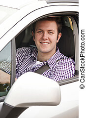 Portrait Of Young Male Driver Looking Out Of Car Window