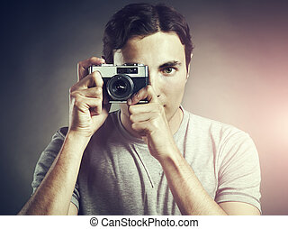 Portrait of young male photographer with a camera
