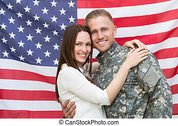 Male Soldier With His Wife In Front Of American Flag