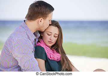 Portrait of young man and woman kissing on a beach