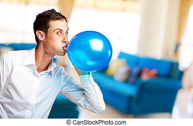 Portrait Of Young Man BlowingBalloon, Indoor