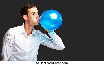 Portrait Of Young Man BlowingBalloon On Black Background
