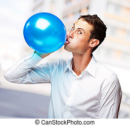 Portrait Of Young Man BlowingBalloon, Outdoor