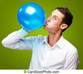 Portrait Of Young Man BlowingBalloon On Green Background
