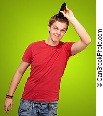 portrait of young man cutting his hair over green background