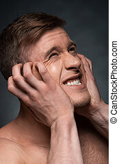 Portrait of young man expressing negative emotions. Scratching his face with hand while looking away