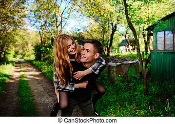 Portrait of young man giving beautiful woman piggyback