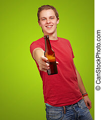 portrait of young man holding beer against a green background