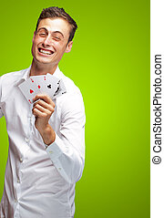 Portrait Of Young Man Holding Poker Cards