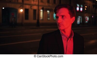 Portrait of young man illuminated by red light standing alone at night in city