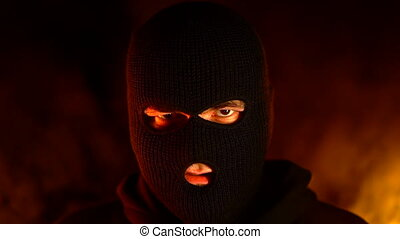 Portrait of young man in black balaclava against backdrop of...
