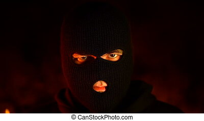 Portrait of young man in black mask during street fights...