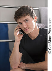 Portrait of Young Man in Black Shirt Calling From Mobile Phone