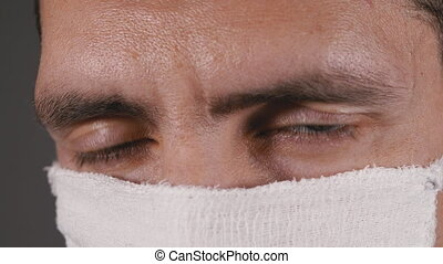 Portrait of a Young Man in a Protective Homemade Gauze Mask for Protection Coronavirus COVID-19. Pandemic. Close-up. The face of men in a mask. Concept health and safety, H1N1, quarantine, virus. Slow Motion