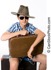 Portrait of young man in sunglasses with a suitcase