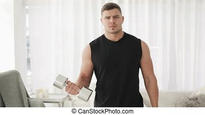 Domestic strength workout. Portrait of young man bodybuilder is lifting dumbbells at home practicing biceps exercise looking at camera. Home fitness, training, workout, bodycare and wellness concept.