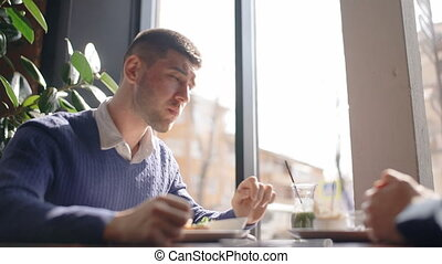 Portrait of young man listening to his partner while having breakfast in cafe.