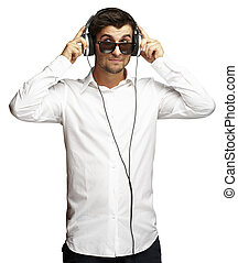 portrait of young man listening to music using headphones over white