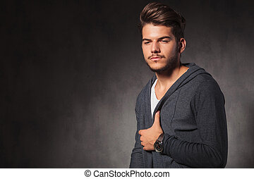 portrait of young man looking down arranging his jacket