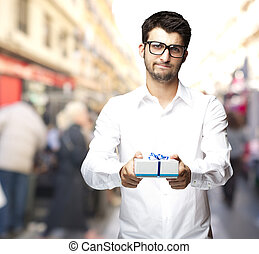 portrait of young man offering a gift at city