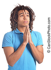 Portrait of young man praying against white background - ...