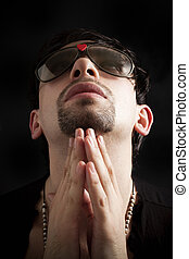Portrait of young man praying in sunglasses