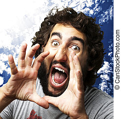 portrait of young man screaming against a cloudy sky background