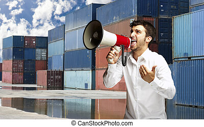 portrait of young man shouting with megaphone at harbor