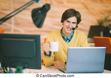 Portrait of young man sitting at his desk in the office