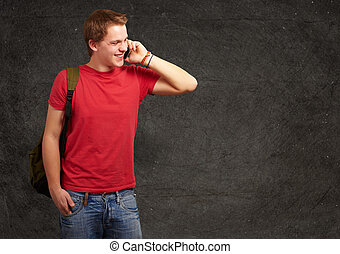 portrait of young man talking on mobile against a grunge wall