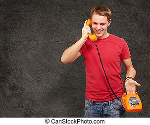 portrait of young man talking on vintage telephone against a grunge wall