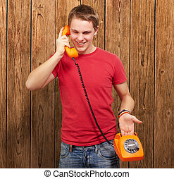 portrait of young man talking on vintage telephone against a wooden wall