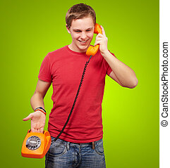 portrait of young man talking on vintage telephone over green background