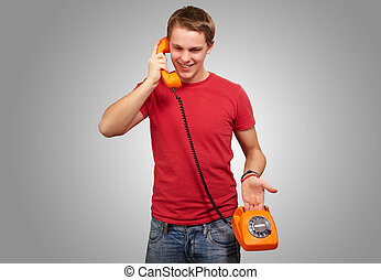 portrait of young man talking on vintage telephone over grey background