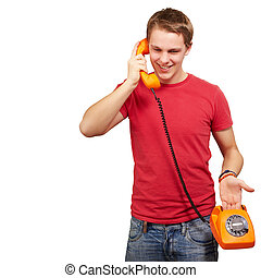 portrait of young man talking on vintage telephone over white background