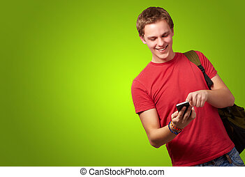 portrait of young man touching mobile screen over green background