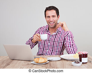 Portrait Of Young Man Using Laptop At Breakfast
