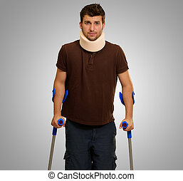Portrait Of Young Man Walking On Crutches On Gray Background