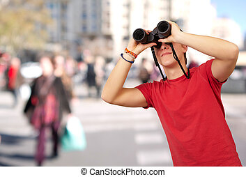 portrait of young man with binoculars at crowded street