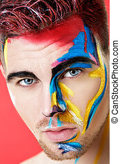 portrait of young man with colored face paint on red...