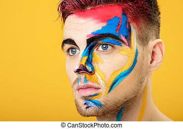 portrait of young man with colored face paint on yellow...