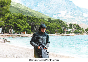 portrait of young man with raincoat jacket on the beach in summer running away from storm approaching from sea. bad weather and cold air climate change forecast