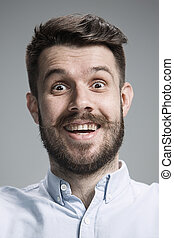 Portrait of young man with shocked facial expression over ...