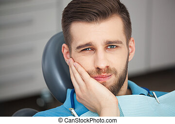 Portrait of young man with tooth pain sitting in a dentist's chair.