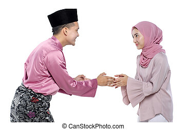 Portrait of young man with traditional clothing shaking hand his wife during hari raya over white background