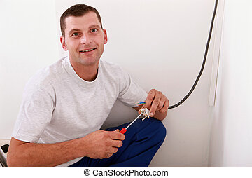 portrait of young man working electrical wiring indoors