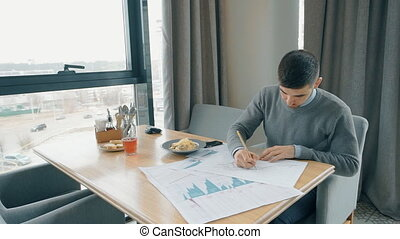 Portrait of young man working on financial graphs in the...
