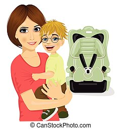 young mother holding little boy with glasses near baby car seat
